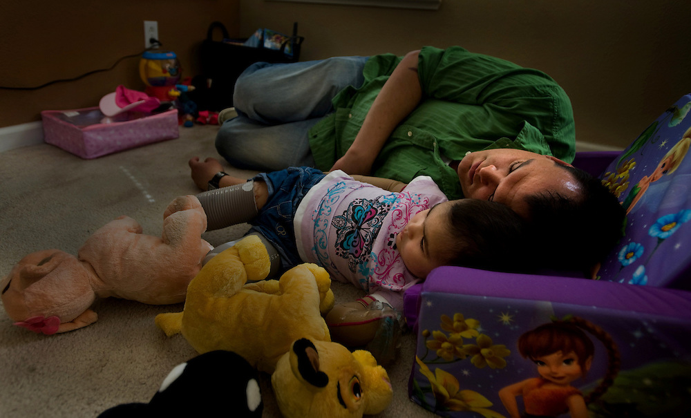 Malyia and her father Ryan nap on their living room floor after an exhausting day of play and physical therapy.