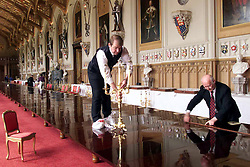 Preparations for the State Banquet in St Georges Hall, Windsor Castle. .Photo by Ian Jones.. Stephen Marshall, Yeoman of the glass and china pantry adjusts the table settings..