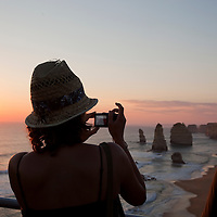 Australia, Victoria, Port Campbell National Park, Silhouette of young woman taking snapshots of Twelve Apostles at sunset