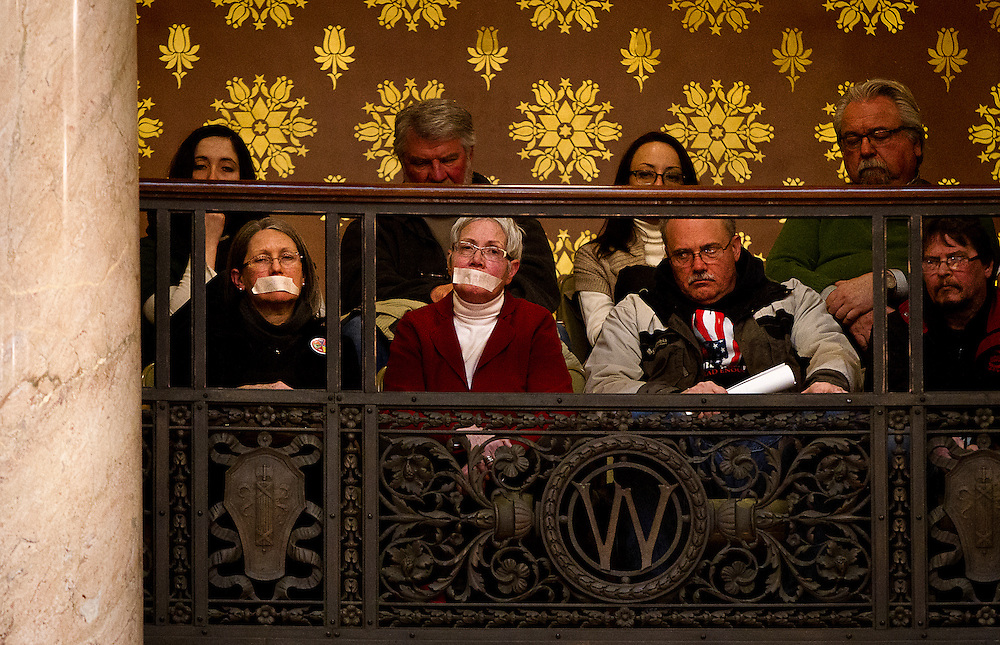 MADISON, WI — FEBRUARY 25: Guests in the gallery of the Wisconsin State Senate with duct-taped mouths look on as the Senate discussed the controversial right-to-work legislation Senate Bill 44.