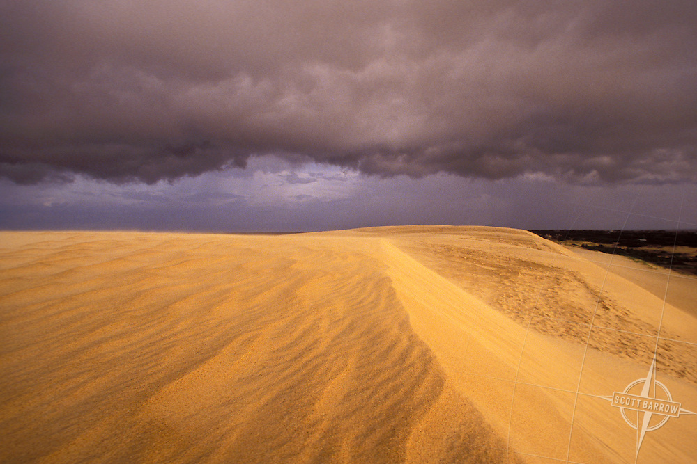 Low storm clouds over wind sculpted sand dunes