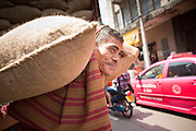 09 JULY 2011 - BANGKOK, THAILAND: A laborer waits to cross a busy street while unloading a truck full of peanuts in burlap bags in the Chinatown section of Bangkok, Thailand. Chinatown is the entrepreneurial hub of Bangkok, with thousands of family owned businesses selling wholesale merchandise in everything from food like rice, peanuts and meats, to dry goods like toys and shoes.  PHOTO BY JACK KURTZ
