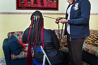 CASERTA, ITALY - 25 FEBRUARY 2015: A Nigerian woman makes braids for her fellow countrywoman at Casa Rut, a shelter for abused young immigrant women in Caserta, Italy, on February 25th 2015. Both women are ex-sex workers staying at Casa Rut.<br /> <br /> Casa Rut was founded in 1995 and it is promoted and managed by the Ursuline Sisters of the Sacred Heart of Mary of Breganze (Vicenza, Italy).  Casa Rut's goal is to provide young immigrant women a familiar environment where  they are helped to protect and free themselves, and to undertake a common path aiming to the integration in Italy's society.