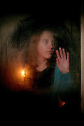 A girl with a candle looks out of a window for someone to return.