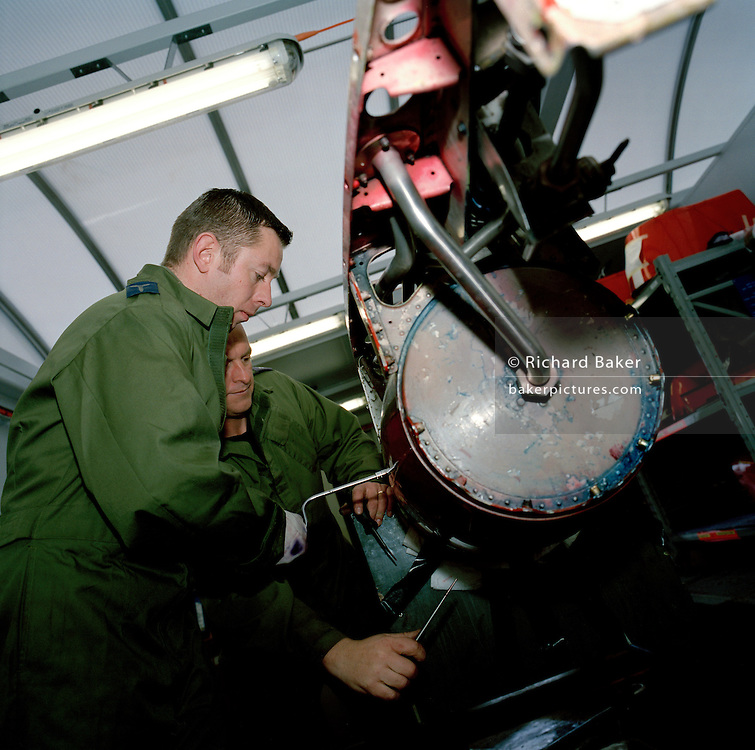Engineering ground staff of the Red Arrows, Britain's RAF aerobatic team, perform scheduled maintenance on Hawk equipment.