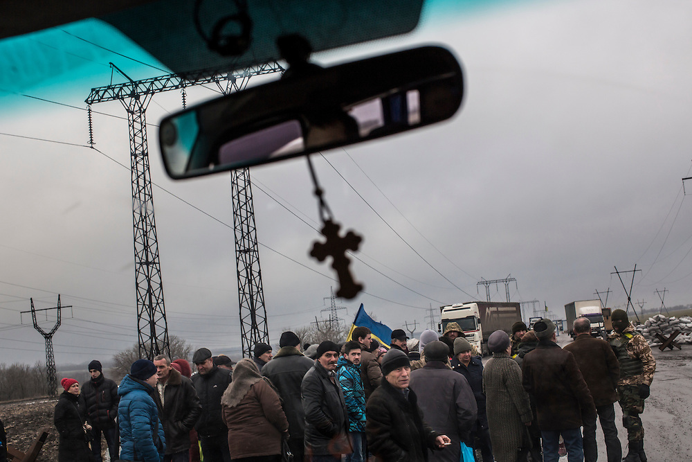 KURAKHOVO, UKRAINE - FEBRUARY 4, 2015: A crowd forms at a Ukrainian military checkpoint in Kurakhovo, Ukraine. Recently-implemented rules require people who wish to travel in and out of rebel-controlled areas of Eastern Ukraine travel to one of a few points, including this checkpoint, to apply for a pass that will allow them free travel between Ukrainian-controlled and rebel-controlled territory. CREDIT: Brendan Hoffman for The New York Times