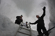 Tourists in April descend by ladder to explore ice cave formed inside glacier by annual meltwaters outside Longyearbyen on Spitsbergen island, Svalbard, Norway.