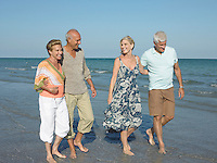 Two senior couples walking barefoot on beach