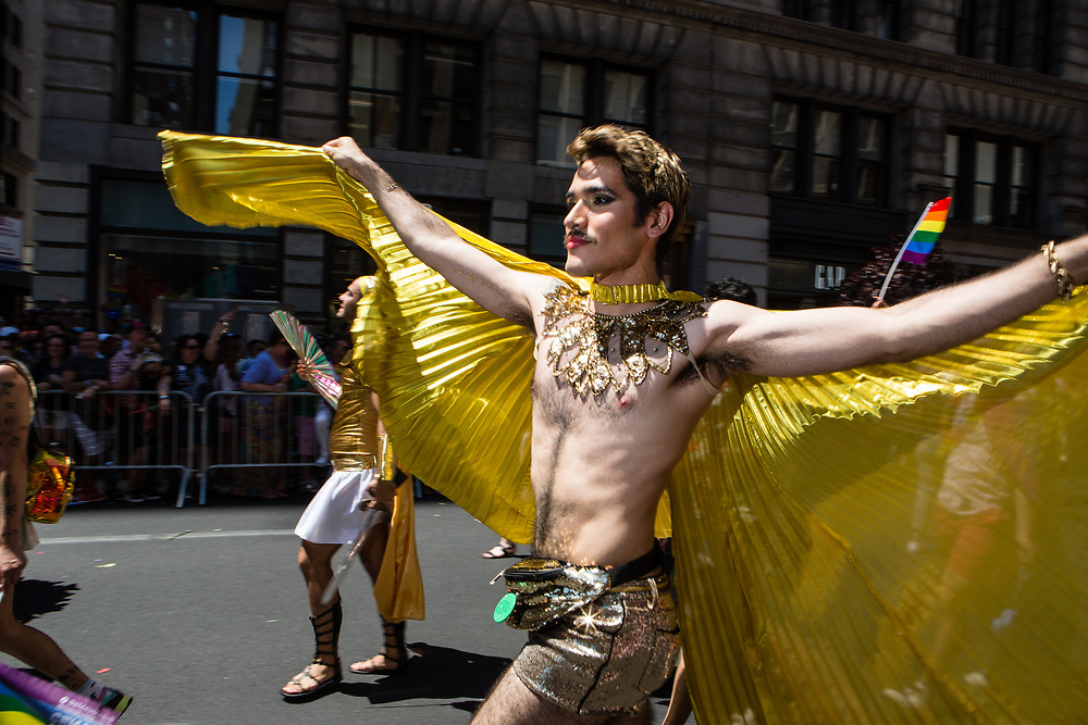 New York, NY - 30 June 2019. The New York City Heritage of Pride March filled Fifth Avenue for hours with participants from the LGBTQ community and it's supporters. A man wears a gold cape.