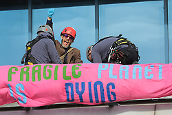 © Licensed to London News Pictures. 10/10/2019. London, UK. An Extinction Rebellion protester is removed from the roof of London City Airport. Protesters plan to occupy the terminal building in a 'Hong Kong-style' shutdown as part of ongoing protests calling on government departments to tackle the Climate Emergency. Photo credit: Rob Pinney/LNP