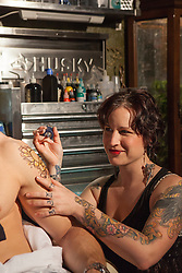 female tattoo artist working on a man's arm