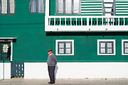 Local man by bright painted house in Costa Nova do Prado, a village with many holiday homes, near Aveiro,  Portugal