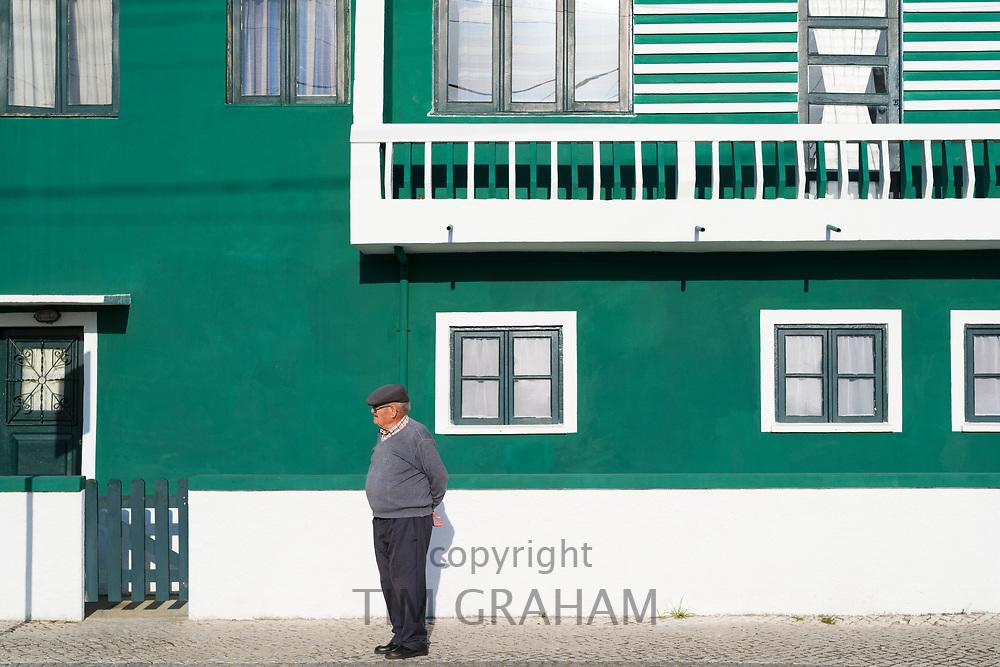 Local man by bright painted house in Costa Nova do Prado, a village with many holiday homes, near Aveiro,  Portugal