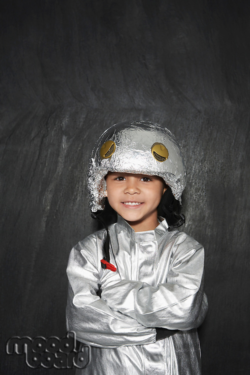 Portrait of young boy (5-6) in astronaut costume crossed arms smiling studio shot