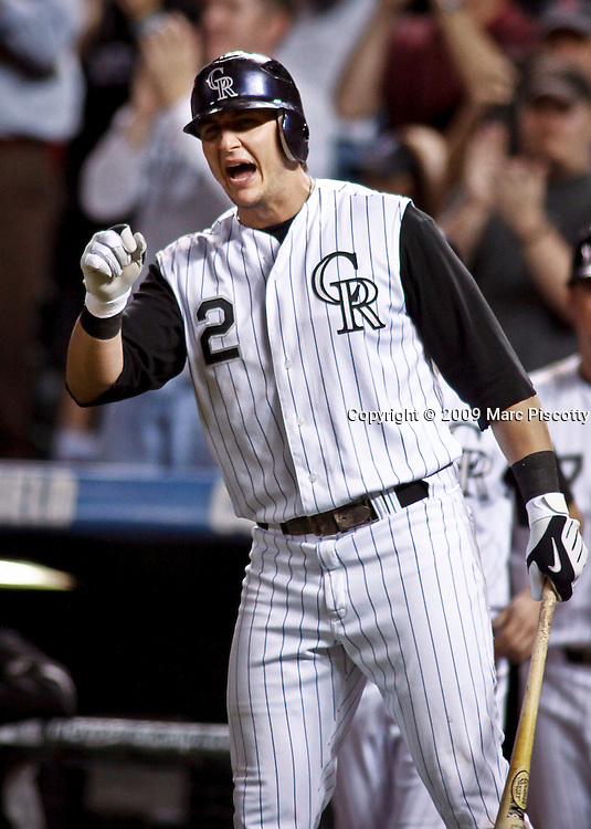 SHOT 9/29/09 8:14:59 PM - Colorado Rockies short stop Troy Tulowitzki gets ready to high five a teammate after they scored against the Milwaukee Brewers at Coors Field in downtown Denver, Co. The Rockies won the game 7-5 in the 11th inning when Rockies' pinch hitter Chris Iannetta hit a walk-off two run game winning home run. The win lifted the Rockies to a three game lead in the race for the NL Wild Card spot over the surging Atlanta Braves. (Photo by Marc Piscotty / © 2009)