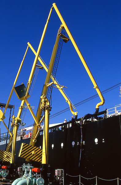 Stock photo of large cranes doing work on the side of a large ship