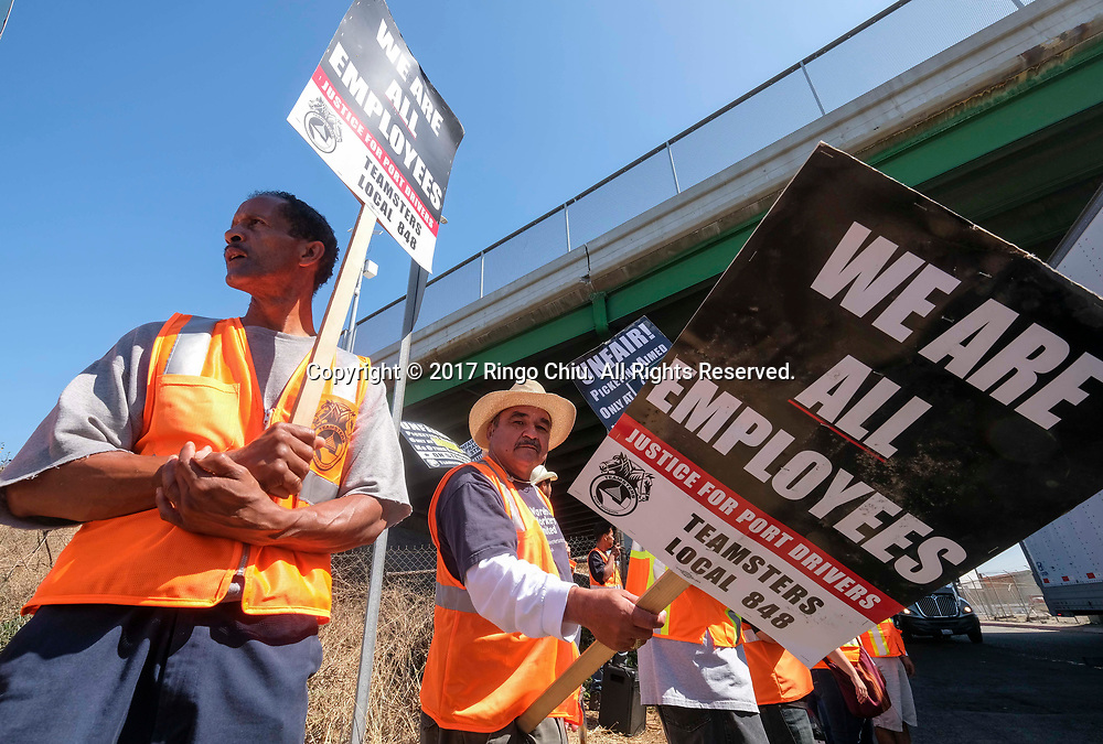 Warehouse workers with pickets strik in front of the Cal Cartage warehouse on port land in Wilmington. (Photo by Ringo Chiu)<br /> (Photo by Ringo Chiu)<br /> <br /> Usage Notes: This content is intended for editorial use only. For other uses, additional clearances may be required.
