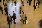 man standing still among fast moving business commuters