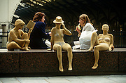 Female colleages enjoy chat and lunch in the city alongside art installation of women at the beach.