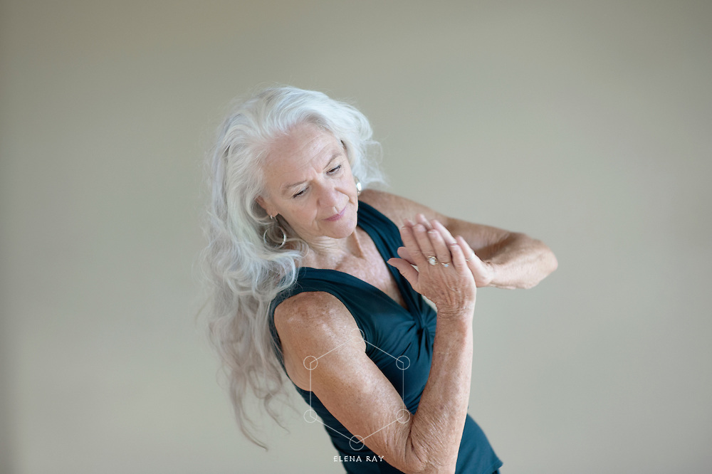 Beautiful mature woman moving mindfully in a creative dance.