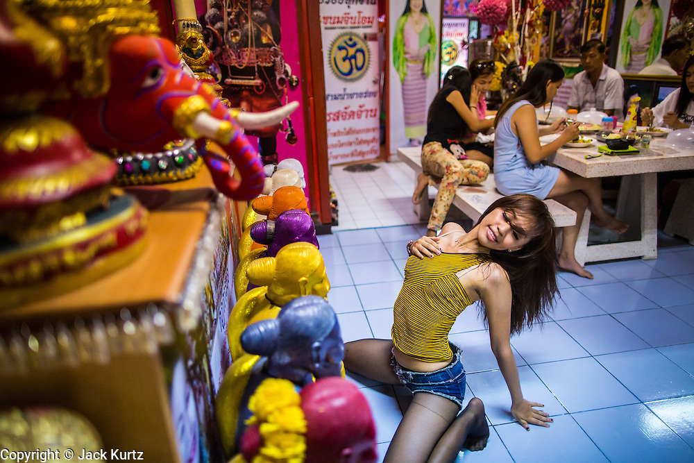 "03 MARCH 2013 - BANGKOK, THAILAND:    KWANT (stage name) a ""coyote dancer"" from the Never Die dance troupe, performs for Chuchok while women eat their lunch in the shrine. The troupe usually performs in pubs and at fairs. The Chuchok Shrine is in suburban Bangkok. More than 100 people a week come to the shrine to pray for good fortune or good health. People whose prayers are answered return to the shrine with ""coyote dancers"" to make merit and thank Chuchok. Coyote dancing is a Thai phenomenon created after the US movie ""Coyote Ugly"" where attractive young women dance in a sexually suggestive way, usually for pay. They're common at bars and festivals. Coyote dancers are typically better paid than other Thai women in the hospitality industry and usually are not allowed to date or see customers are off the dance floor. Coyote dancers perform at the Chuchok shrine because according to Buddhist literature Chuchok was a relatively repulsive old hermit and Brahmin priest who was cared for by a young woman after he made her family's wishes come true.PHOTO BY JACK KURTZ"