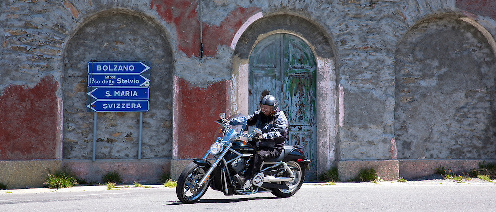 Motorcyclist on Harley Davidson motorbike drives The Stelvio Pass, Passo dello Stelvio, Stilfser Joch, to Bormio, Northern Italy