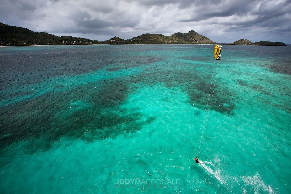 Kiteboarder soars across turquoise lagoon under a menacing sky near Grenada, Caribbean.  I took this shot from the top of our mast, about 80 feet off the water.