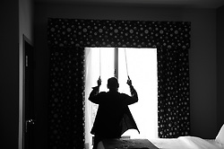 "WILSON, NC  - JUNE 7: Billy Kaye closes the curtain in his hotel room in Wilson, NC, June 7, 2018, before getting dressed for his upcoming concert at the Vollis Simpson Whirligg Park. He changes his clothes one more time to look as his best. Appearance is important for Billy. Like many other Jazz musicians of his generation he follows the rule ""you are always first seen before heard"". Kaye is visiting his hometown where he will perform for the first time. His performance will be part of a two-day long celebration, organized by The North Carolina Arts Council, The Arts Council of Wilson, The Vollis Simpson Whirligig Park, and The Jazz Revival Project, of his life and achievements as one of the US's most legendary Jazz drummers. (Astrid Riecken)"