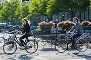 Young people in casual clothes cycling across bridge in Amsterdam, Holland