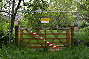 As the UK's Coronavirus pandemic lockdown continues into its 5th week, and UK deaths from Covid-19 reached 21,678 - a daily rise of 586, a gate is taped-off while seasonal rain empties Ruskin Park in Lambeth, where until now, this green space in south London has been busy with those exercising according to social distance requirements, on 28th April 2020, in London, England.