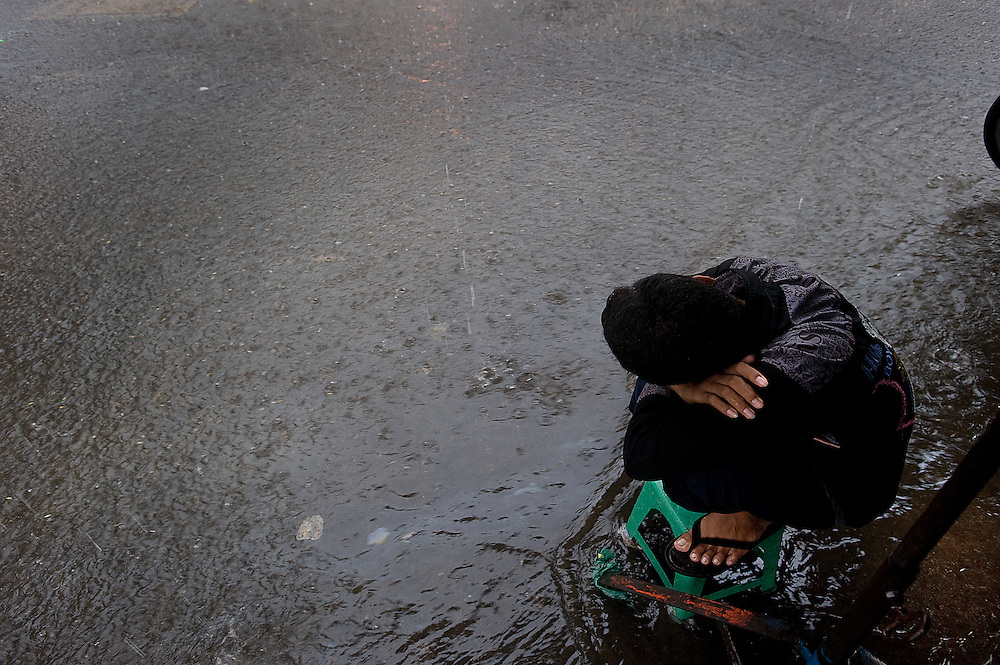 A flash storm hits Phnom Phen as a child gets caught during the Monsoon season and takes a rest from the flooded street.