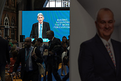 © Licensed to London News Pictures . 02/10/2017. Manchester, UK. Delegates watch Chancellor PHILIP HAMMOND deliver his keynote speech on a big screen in the exhibition hall , during the second day of the Conservative Party Conference at the Manchester Central Convention Centre . Photo credit: Joel Goodman/LNP