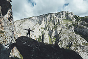 Silhouette of a climber gathering ropes with white mountains on background Mamut climbing athlete Bobbi Bensman enjoying a climbing trip at Roca Verde, Asturias, Spain