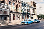 Two Blue Vintage 1950s Cars driving in Havana, Cuba