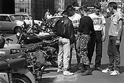 Oost Duitsland, DDR, Leipzig, 1-7-1990 Op 1 juli 1990 werd de duitse monetaire eenwording effectief. De burgers van de ddr konden hun marken, ostmarken, inwisselen tegen de west-duitse mark, in winkels vond een grote operatie plaats om prijzen aan te passen en westerse producten in de schappen te leggen. Jongeren hangen wat bij een paar brommers en motoren die op straat geparkeerd zijn. Straatbeeld, stadsbeeld.Foto: Flip Franssen/Hollandse Hoogte