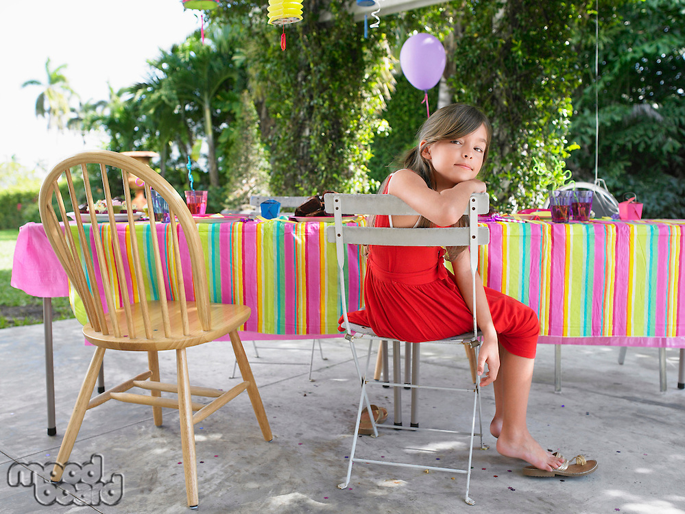 Portrait of girl (7-9) sitting at table after birthday party