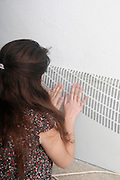 Young woman (25-29) warms her hands on a radiator