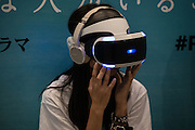 """A young girl experiences a Sony PlayStation VR headset during a preview at the exhibition """"Odaiba Dream Experience presented by PlayStation VR'' at the Fuji Television Headquarters Building, in Tokyo. 26/07/2016-Tokyo, JAPAN"""