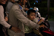 A young boy passenger on a motorcycle at night in Ho Chi MInh City, Vietnam, Southeast Asia