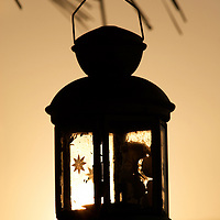 Oman, Wahiba Sands. January/24/2008...The glow of a setting sun in a lantern used in lieu of electrizity at the Nomadic Desert Camp.