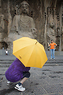 Tourists taking pictures in front of a Buddha statue at Longmen caves near Luoyang. The site is inscribed as a Unesco World Heritage Site.