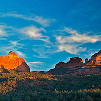 The evening sun sets on the surrounding red rock next to Oak Creek Canyon, near Sedona, Arizona.