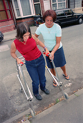 Mother helping daughter with Cerebral Palsy using frame to mount pavement kerb,