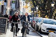 In Utrecht rijden fietsers langs de Oudegracht in de binnenstad. Twee vrouwen fietsen al pratend naast elkaar.<br /> <br /> In Utrecht cyclists ride at the Oudegracht.
