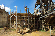 Builder on the scaffolding lowering a crate using a lifting device, at the Chateau de Guedelon, a castle built since 1997 using only medieval materials and processes, photographed in 2017, in Treigny, Yonne, Burgundy, France. The Guedelon project was begun in 1997 by Michel Guyot, owner of the nearby Chateau de Saint-Fargeau, with architect Jacques Moulin. It is an educational and scientific project with the aim of understanding medieval building techniques and the chateau should be completed in the 2020s. Picture by Manuel Cohen