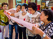 "22 AUGUST 2017 - BANGKOK, THAILAND: Women look at a prayer scroll during a ceremony on the first day of Hungry Ghost Month at the Poh Teck Tung Shrine in Bangkok's Chinatown. The seventh lunar month (August - September) is when many Chinese believe Hell's gate will open to allow spirits to roam freely in the human world. Many households and temples hold prayer ceremonies throughout the month-long Hungry Ghost Festival (Phor Thor) to appease the spirits. During the festival, believers will also worship the Tai Su Yeah (King of Hades) in the form of paper effigies which will be ""sent back"" to hell after the effigies are burnt.      PHOTO BY JACK KURTZ"