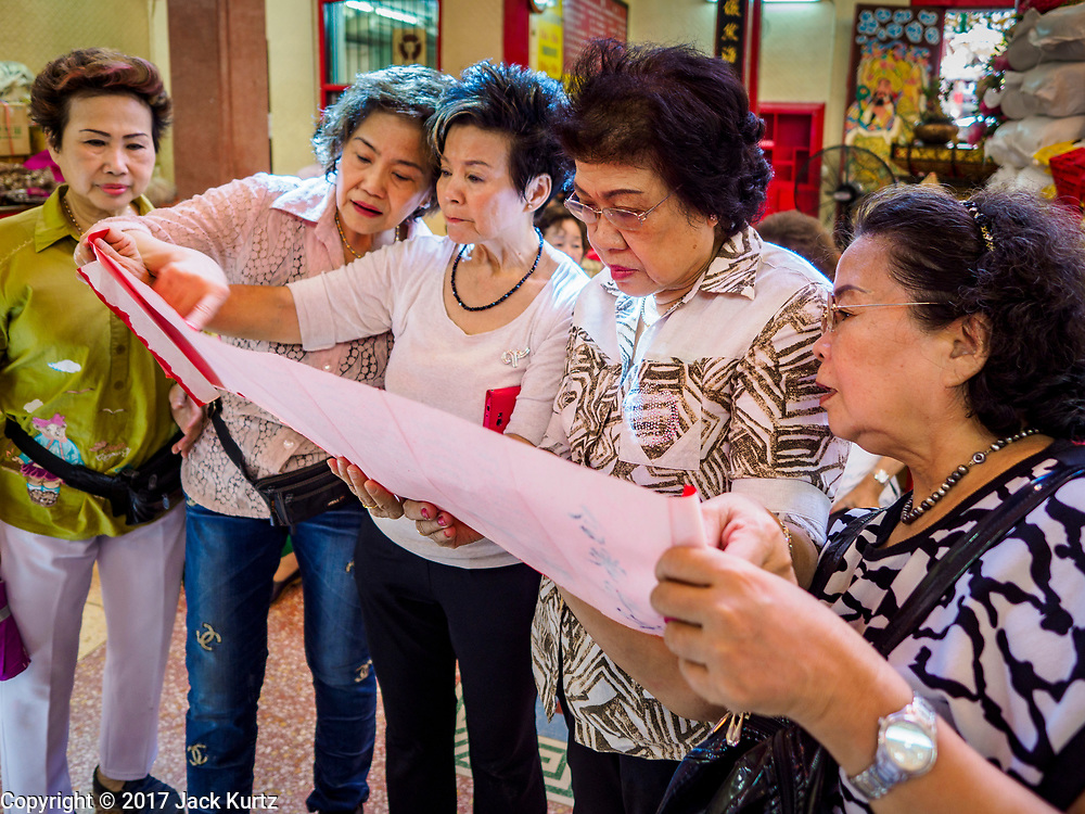 """22 AUGUST 2017 - BANGKOK, THAILAND: Women look at a prayer scroll during a ceremony on the first day of Hungry Ghost Month at the Poh Teck Tung Shrine in Bangkok's Chinatown. The seventh lunar month (August - September) is when many Chinese believe Hell's gate will open to allow spirits to roam freely in the human world. Many households and temples hold prayer ceremonies throughout the month-long Hungry Ghost Festival (Phor Thor) to appease the spirits. During the festival, believers will also worship the Tai Su Yeah (King of Hades) in the form of paper effigies which will be """"sent back"""" to hell after the effigies are burnt.      PHOTO BY JACK KURTZ"""