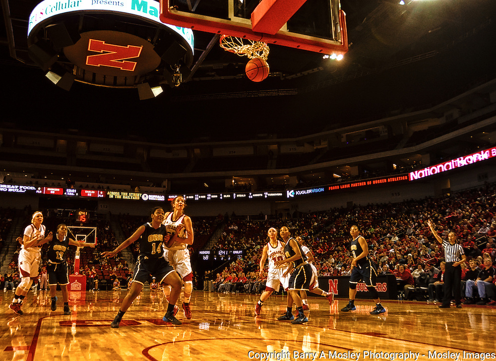 Wide view of collegiate women basketball players watch as ball goes through the net. Image captured by Barry A Mosley Photography, Lincoln, Nebraska.