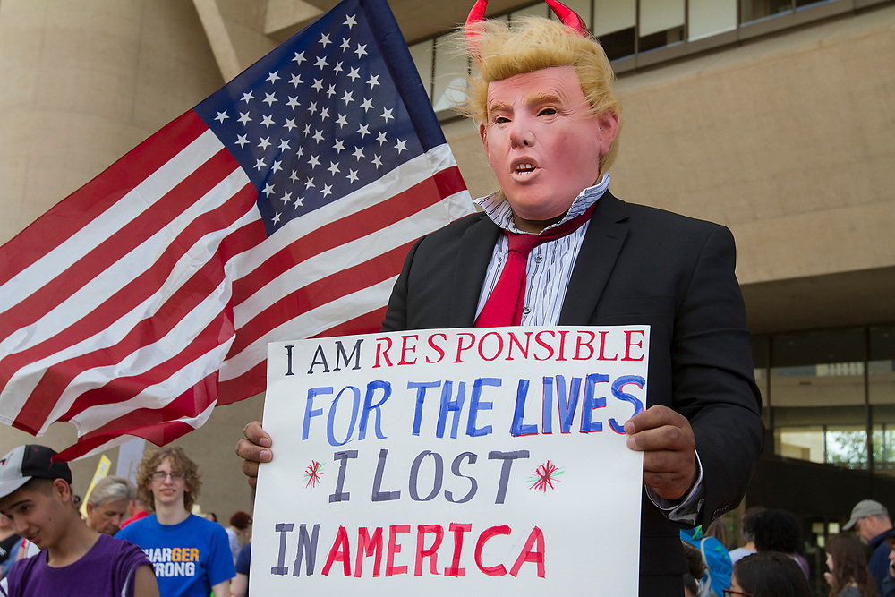 A protester donning a costume resembling President Donald Trump stands in front of Dallas City Hall during the March for our Lives in downtown Dallas.