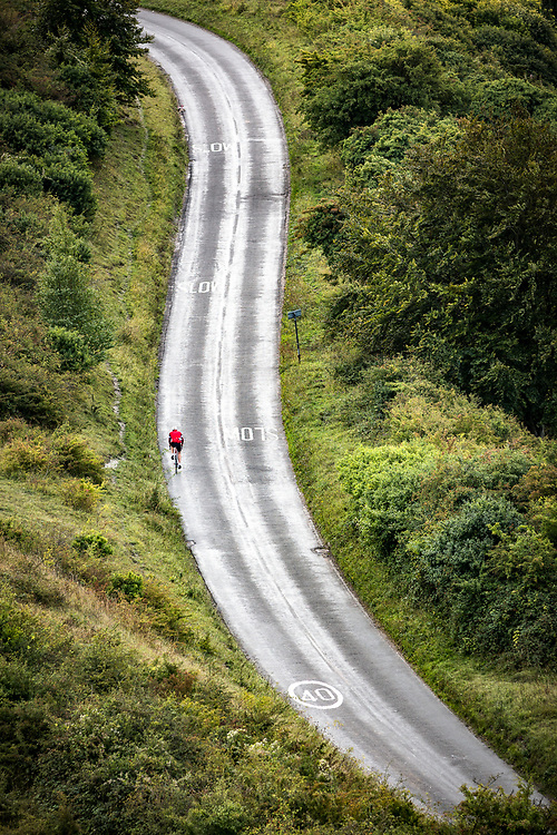 A solo cyclist climbs Ivinghoe Beacon hill. With its steep climb this is a popular spot for road cyclists.